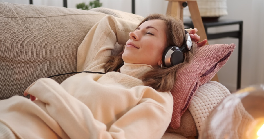 Woman relaxing and listening to music on sofa | Shutterstock HD Video #1046984383