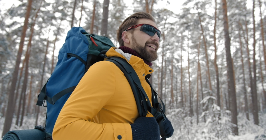 Happy bearded man in warm clothing and mirrored eyeglasses enjoying beautiful winter weather while walking with big blue backpack in snowy forest. Concept of travelling and adventure. | Shutterstock HD Video #1047009313
