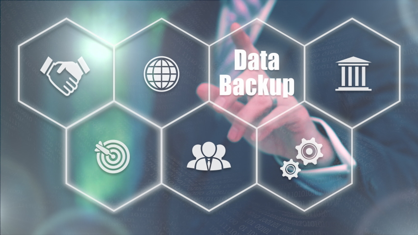 A businessman selecting a Data Backup business concept from a display of white hexagon shapes and symbols with a blue tint. | Shutterstock HD Video #1047025513