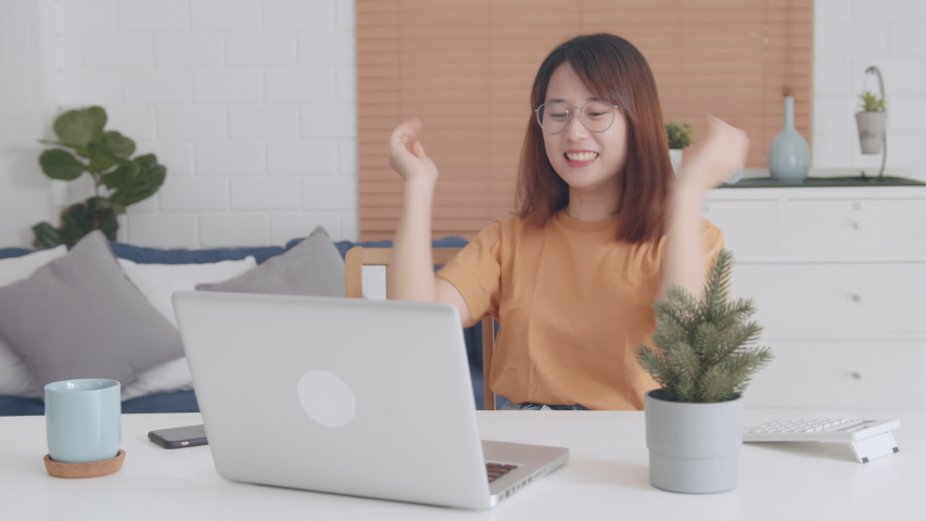 Attractive Young Asian Woman Celebrating success after receiving good news. Happy Female Freelancer feeling Excited Clipping hand and Arm raised celebrate win lottery victory prize, or job promotion. | Shutterstock HD Video #1047074263