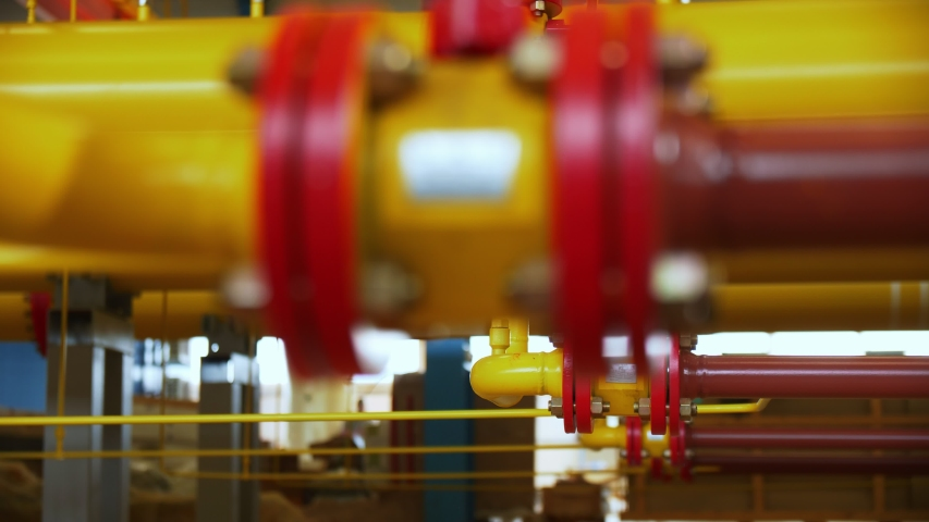 Bright colored pipes of gas transporting system connected with flanges at modern automated compression station | Shutterstock HD Video #1047101743