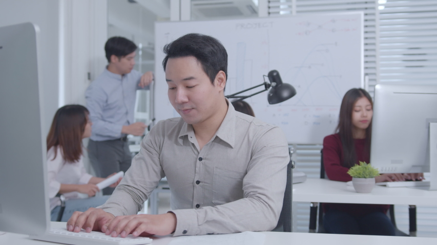 Excited Asian Businessman Sitting at his office desk arms raised celebration of successful project, job promotion. His Colleagues are Clapping and Happy. Successful Businessman Concept. | Shutterstock HD Video #1047146533