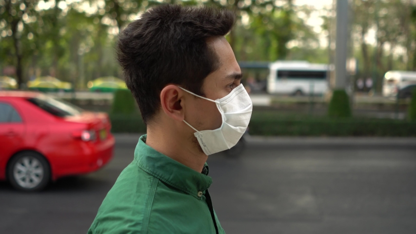 A man wearing mask protective for spreading of disease virus Covid-19 and air smog pollution with PM 2.5 with coughing  while walking on street at Chatuchak district in  Bangkok city, Thailand. | Shutterstock HD Video #1047320383