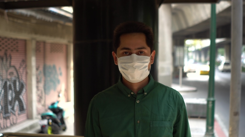 A man wearing mask protective for spreading of disease virus Covid-19 and air smog pollution with PM 2.5 while walking on street at chatuchak district in  Bangkok city, Thailand. | Shutterstock HD Video #1047323593