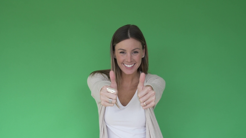 Portrait of cheerful woman showing thumbs up on green background, isolated | Shutterstock HD Video #1047332713