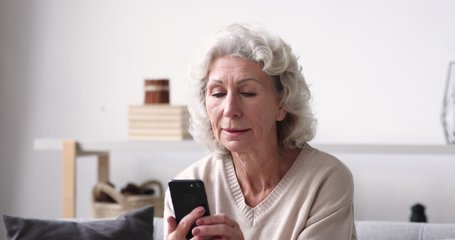 Smiling senior adult grandmother using smartphone sitting on sofa. Happy 70s elder woman holds mobile phone texting message, checking app, reading news at home. Old grandparent learns tech gadget