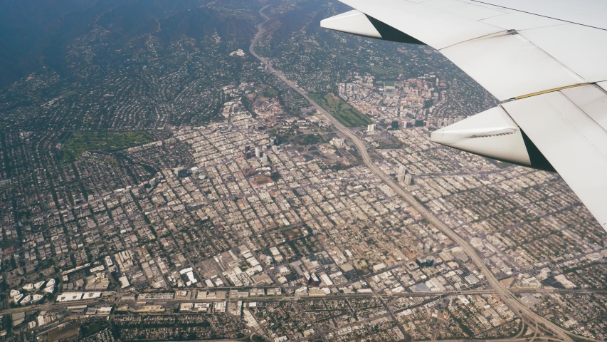 View from window of the plane flying above Los Angeles city. Areas of city with a highway to Las Vegas and many blocks, houses, residential buildings. | Shutterstock HD Video #1049157673