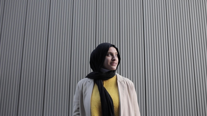 Smiling woman wearing hijab and looking up in front of a wall | Shutterstock HD Video #1049571493