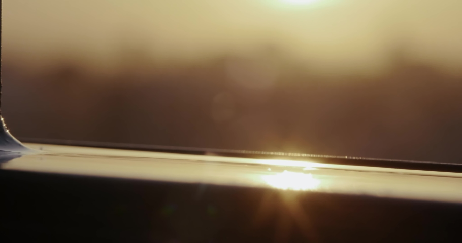 Close-up of drops of melting snow, drops of water dripping from roof onto metal railing, glare of setting sun on metal, yellow sunset colors, abstract plan, spring has come, self-isolation, quarantine | Shutterstock HD Video #1049582563