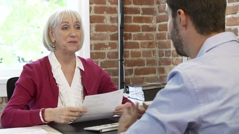 Older businesswoman interviewing younger male candidate for job and reviewing resume.Shot on Sony FS700 in PAL format at a frame rate of 25fps