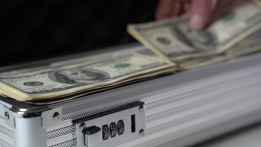Dollar bills are put in a metal suitcase. Close-up | Shutterstock HD Video #1049640823