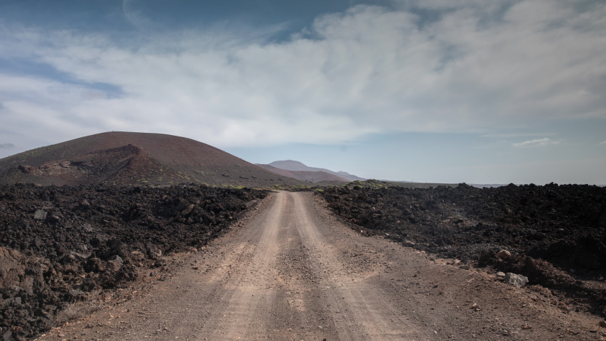 Timelapse of clouds passing over wild arid landscape with a gravel road of the Timanfaya National Park in Lanzarote. | Shutterstock HD Video #1049653423