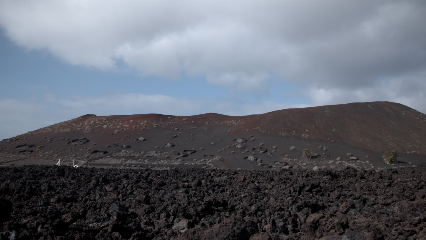 Clouds passing over wild arid landscape of the Timanfaya National Park in Lanzarote. | Shutterstock HD Video #1049661313
