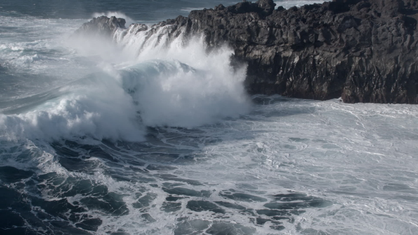 Powerful waves breaking on the cliffs at Los Hervideros in the Canary Islands in slow motion | Shutterstock HD Video #1049663953
