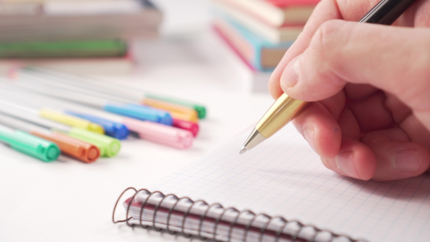 Hand writes with a black golden pen in a notebook on a white table with multi-colored school supplies for creativity and books. Coronavirus Quarantine Distance Learning | Shutterstock HD Video #1049738143