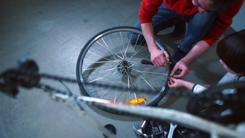 A father is repairing a wheel with his son. Remove the tire, tire from the wheel rim. Bike repair. Useful leisure. Distance, online school. | Shutterstock HD Video #1049778943