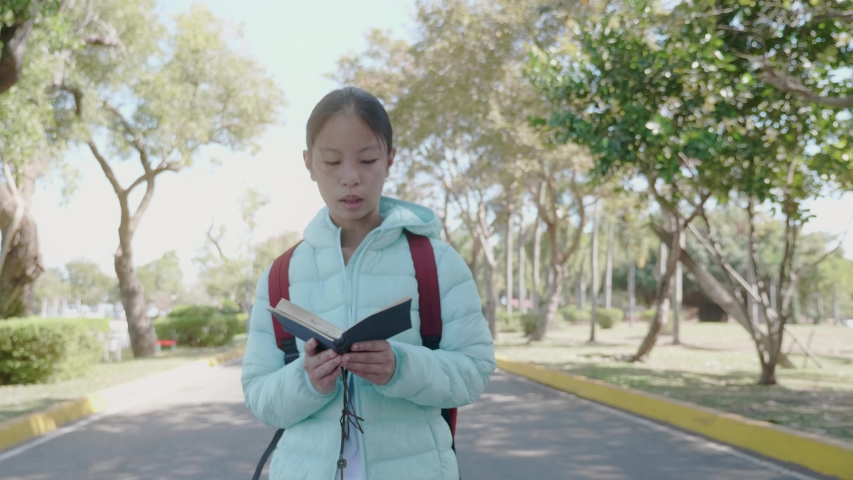 Asian girl reading a book  in the park.  | Shutterstock HD Video #1049790763