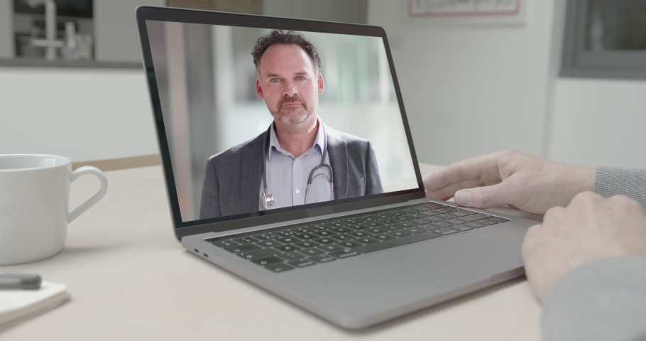 Online video call via laptop of male doctor consulting sick man talking in kitchen. Medicine, healthcare, Technology | Shutterstock HD Video #1049943043