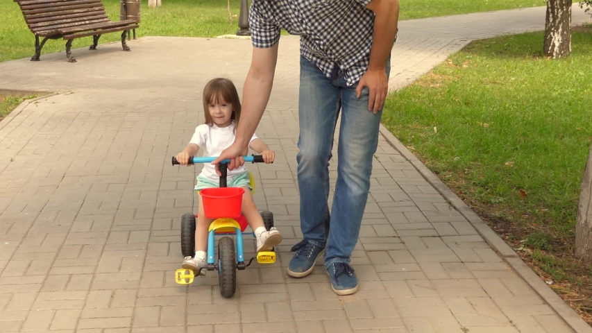 Happy father teaches little daughter to ride bike. Dad plays with his child outdoors. child learns to ride bicycle. concept of happy family and childhood. parents and little daughter walks in park. | Shutterstock HD Video #1049992543