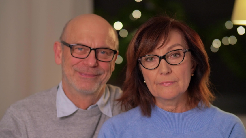 Relationships, old age and people concept - portrait of happy smiling senior couple at home in evening | Shutterstock HD Video #1050019723