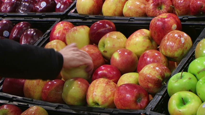 Woman selecting fresh red apples in grocery store produce department.   Shutterstock HD Video #1051648