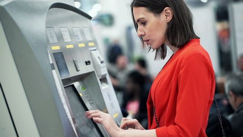 Young woman buying ticket from vending machine at station