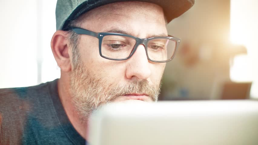 Man with glasses working on laptop computer | Shutterstock HD Video #10523393