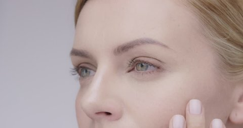 Macro Close up of Beautiful healthy woman touching smooth skin on face in slow motion for beauty skincare concept on a grey background Shot in 6K on RED EPIC DRAGON
