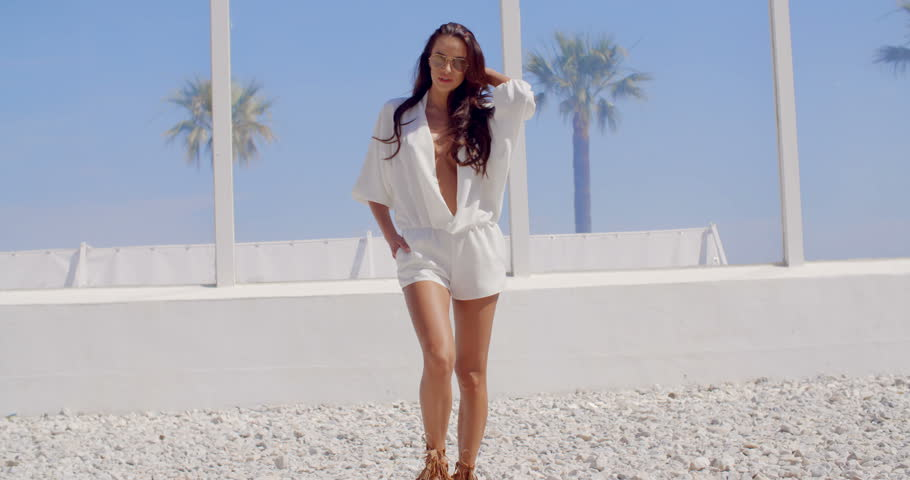 Attractive Brunette Woman with Long Hair Wearing White Shorts Jumpsuit Walking Toward Camera on Tropical Beach on Sunny Day