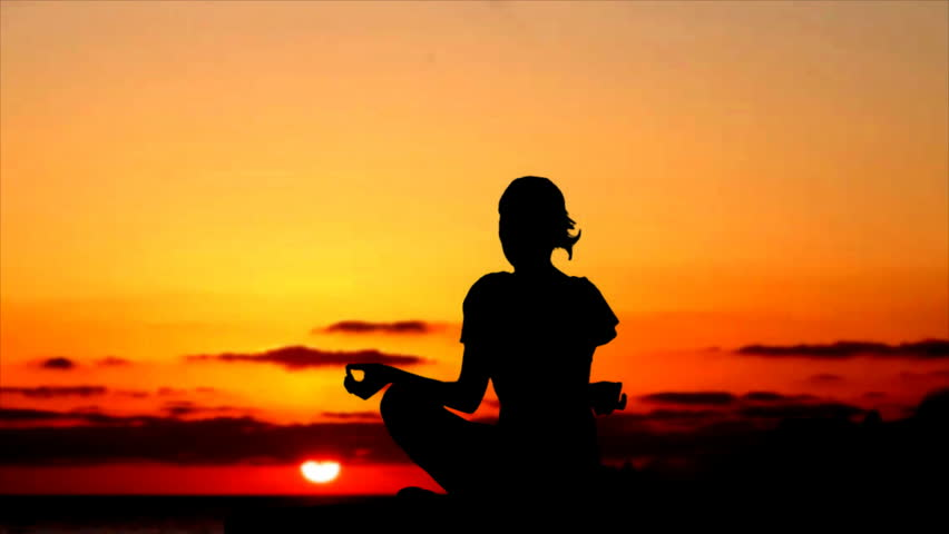Silhouette of woman meditating during sunset