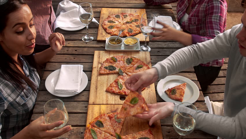4k above video of multicultural group of young friends enjoying a meal, aerial view food pizza meal togetherness concept.