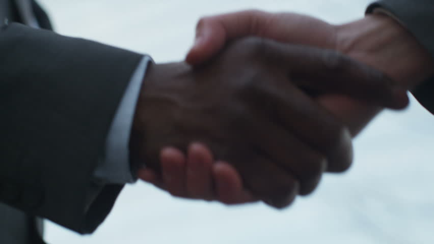 4K Close up on hands of 2 businessmen shaking hands outside city building