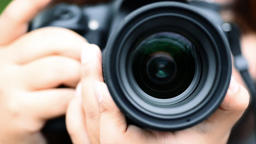 Young woman takes pictures with DSLR camera.