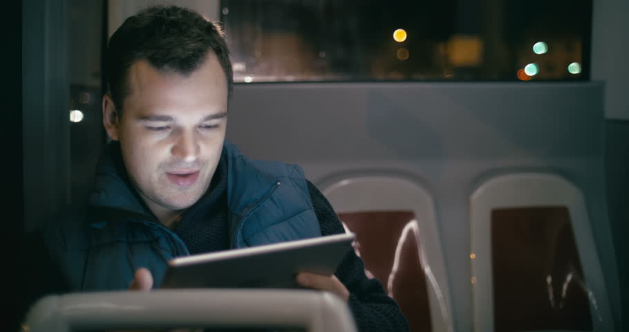 Young smiling man using touch pad during everyday evening bus ride in the city. Entertainment in the trip | Shutterstock HD Video #10643093