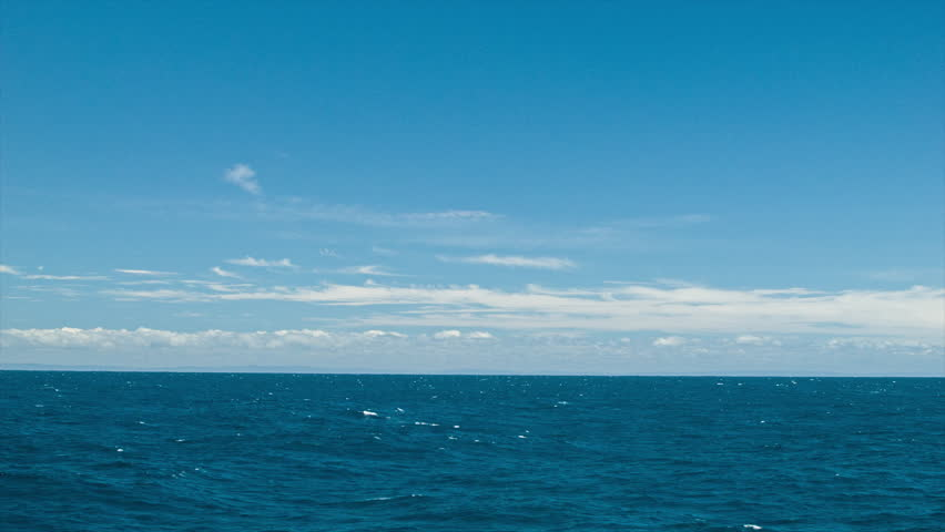 At Sea Wide Shot with Land on the Horizon in Far Distance during a Sunny Day with Blue Sky and White Clouds