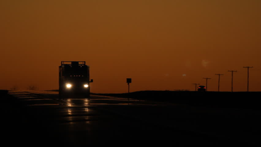Pickup truck pulling large enclosed trailer. Dusk in Saskatchewan. Dusk with orange sky. Pickup truck with trailer approaches and passes. HWY 1 TransCanada highway in Saskatchewan, Canada.