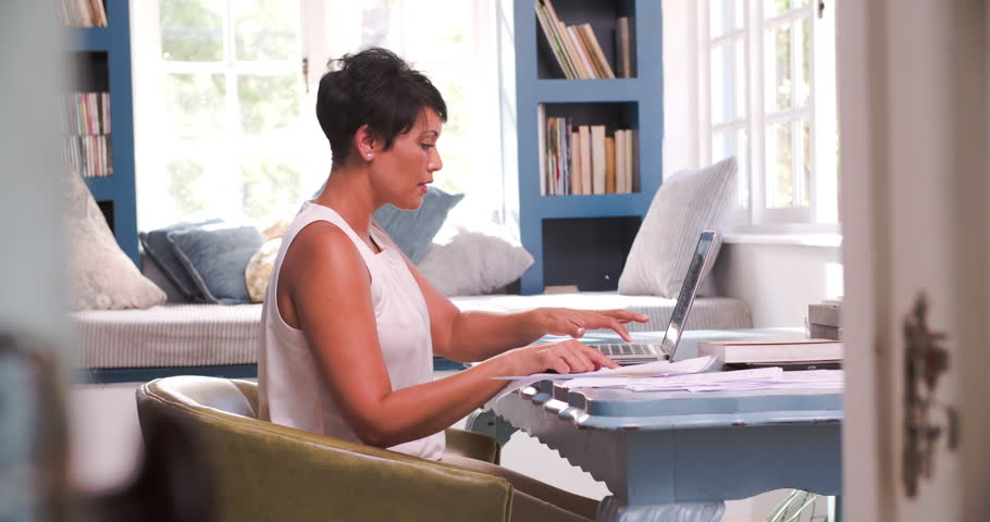 Mature Woman At Desk Working In Home Office With Laptop | Shutterstock HD Video #10690937