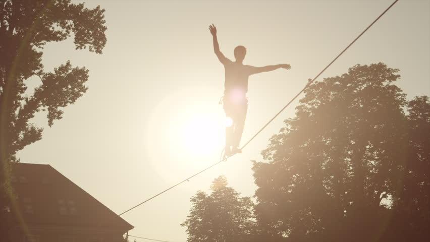 Man balacing on slackline between the houses in big city