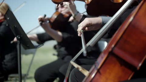 Shot of outdoor orchestra, close up on the musicians playing string instruments.