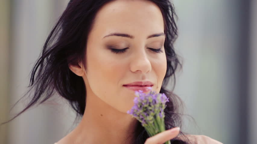 Portrait of a pretty young woman sniffing a bouquet of lavender. Beautiful woman inhales the fragrance of flowers. The girl face close up with a bouquet of lavender.