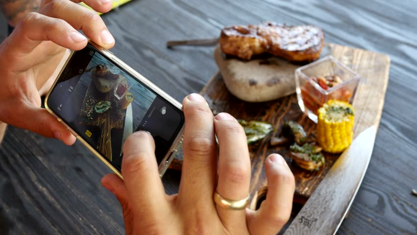 take a photo of food in a restaurant with mobile phone camera for social network | Shutterstock Video #10765553