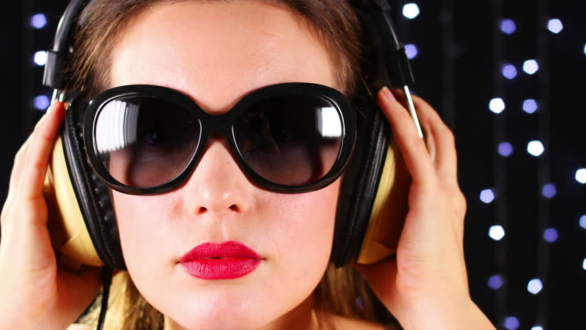close-up of the face of a beautiful woman wearing sunglasses and headphones, listening to music