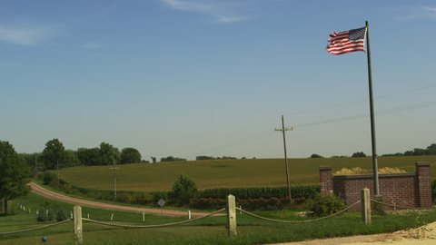 American Flag blowing in front of fields of crops in Nebraska.