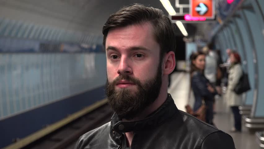 young handsome hipster man waits on metro in subway station - other people in background #10817888