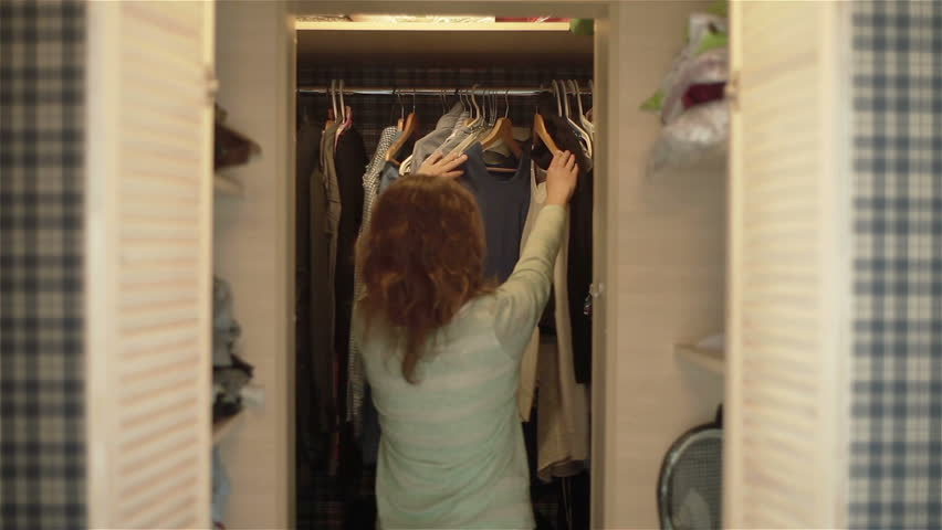 Attractive young women choosing clothes in wardrobe preparing to go out