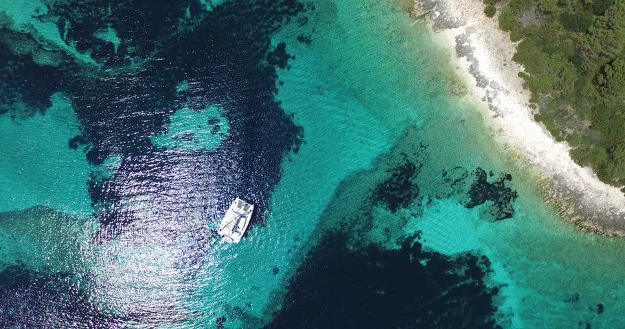 Aerial, top scene of transparent doted shore of a virgin island. Catamaran anchored. Rocky coastline. Paradisiac landscape. Caribbean shore. Drone scene, from aerial to a detail of catamaran.