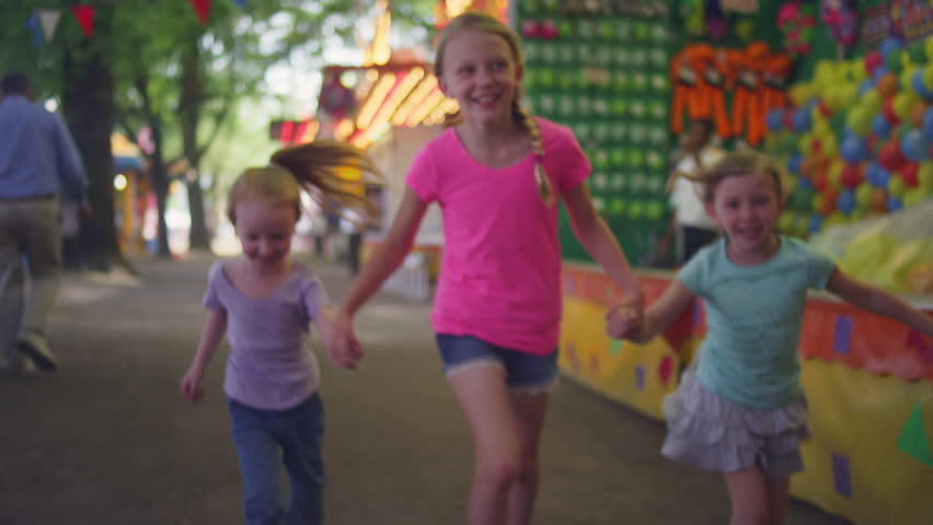 Three little girls running toward the camera at a carnival, slow motion | Shutterstock HD Video #10861316