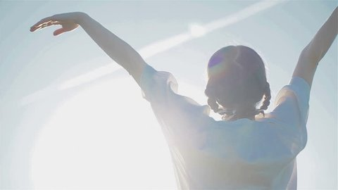 Young woman raising hands up watching at sky with plane trail in it