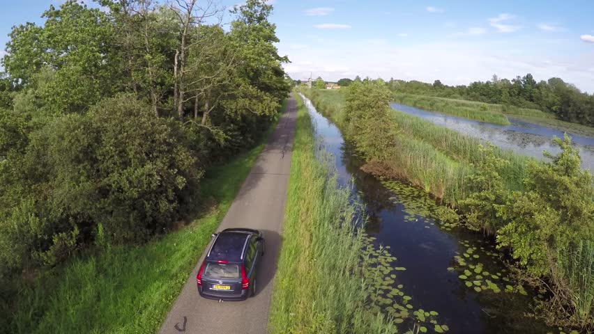 Aerial of a lake river water peatland and then turning to a small concrete road and a blue car passing by underneath the drone camera trees at the side of the road and blue sky 4k high resolution | Shutterstock HD Video #10901693