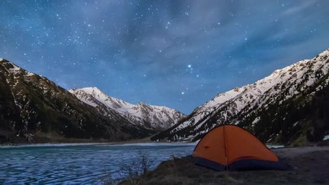 Night timelapse of the big almaty lake in mountains with the tent in front